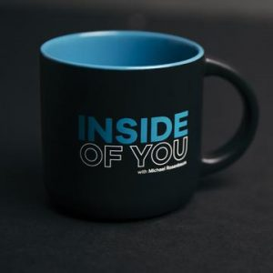 Picture is a close up of a mug saying the name of Michael's podcast